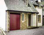 Seceuroglide insulated roller garage door painted burgundy. Fitted to white rendered house with attached garage.\\n\\n27/09/2015 23:06